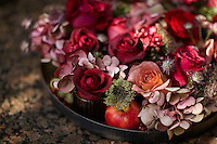 An arrangement of red and pink flowers are displayed in a shallow dish.