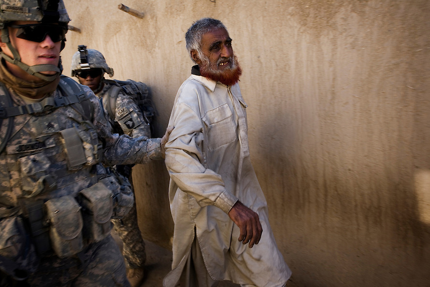 An Afghan man is roughly escorted outside while his home is searched by members of 1/506th Infantry, Scout Platoon in Shamamolzi, Paktika province, Afghanistan, Sunday, Feb. 8, 2009.