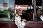 15 June 2013, (NIMA), Dar-al-Aman road, Sanaturiam Kabul Province,  Afghanistan.  An old man leans out of a bus in central Kabul. Picture by Graham Crouch/World Bank
