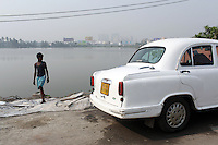 A young Indian boy stands near a car in Kolkata, India. November, 2013
