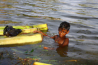 A child swims in the floodwaters beside upturned banana trees. Thousands of people were displaced in Shyamnagar Upazila, Satkhira district after Cyclone Aila struck Bangladesh on 25/05/2009, triggering tidal surges and floods..