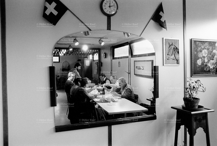 "Switzerland. Geneva. Garbage collectors. Lunch time. Workers sit at a table and eat the ""fondue"" (melted cheese), which is a swiss food speciality. Painting of a horse and flowers, two swiss flags, a watch and a large mirror are on the wall.  © 1991 Didier Ruef"