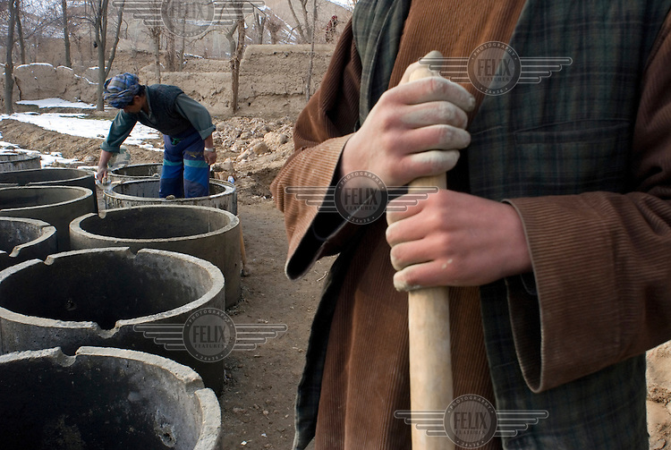 Workers stand beside concrete manhole barrels that are used for well construction. Czech NGO People in Need (PIN), has provided assistance for the construction and maintainance of wells and kandas (reservoirs) across the district. The construction of one well with a hand pump costs USD 2,000..