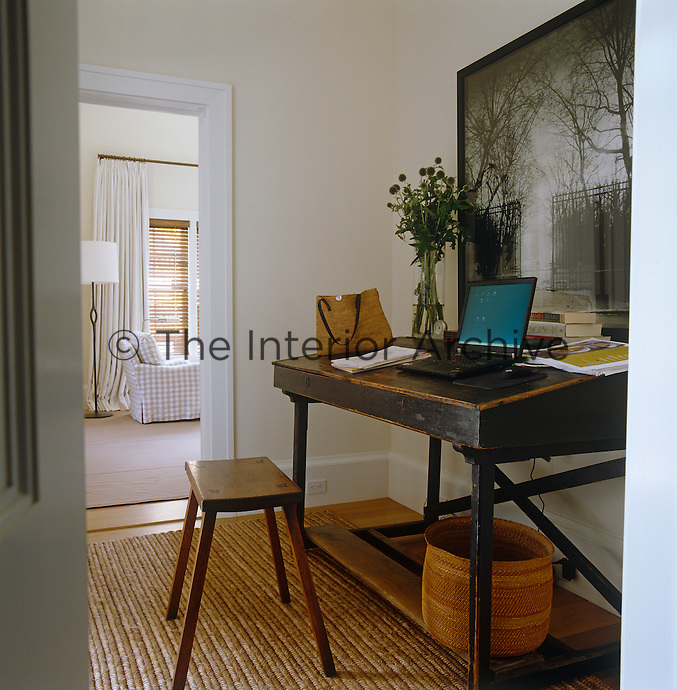 Ina Garten's study is situated in an alcove outside her bedroom; behind the antique desk is a large photograph of the Luxembourg gardens by Jean-Michel Berts