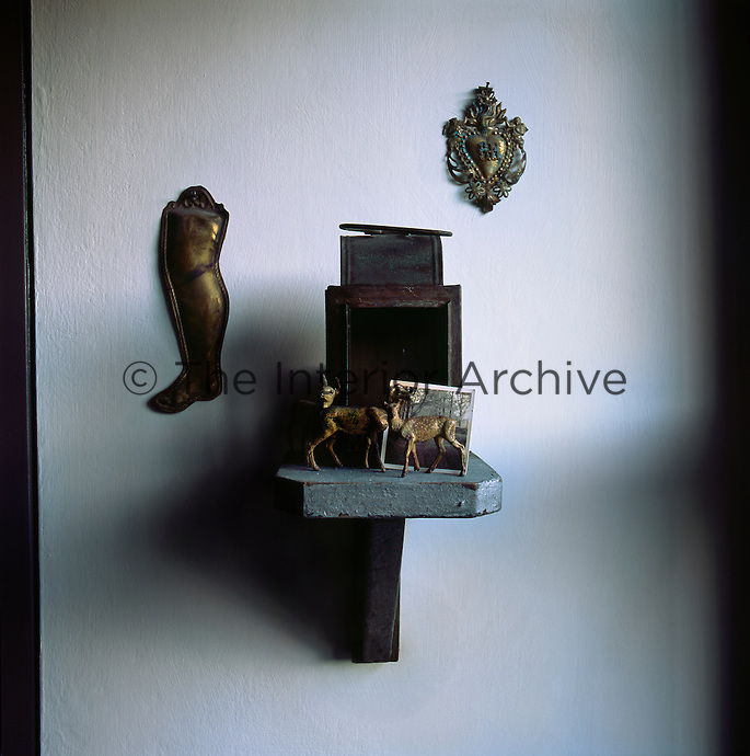 A group of objects are displayed on a wall mounted shelf.