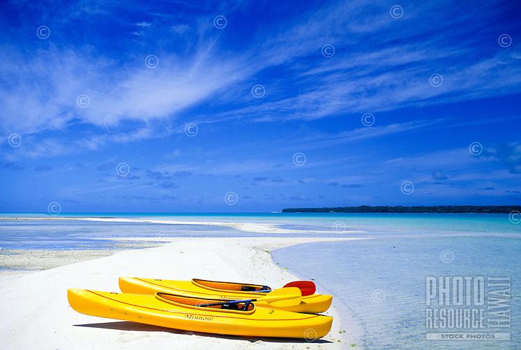 Two kayaks on white sand near a blue lagoon off Aitutaki, Cook Islands