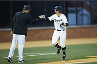Chris Lanzilli (24) of the Wake Forest Demon Deacons bumps fists with head coach Tom Walter (16) as heads towards home plate after hitting a home run against the Sacred Heart Pioneers at David F. Couch Ballpark on February 15, 2019 in  Winston-Salem, North Carolina.  The Demon Deacons defeated the Pioneers 14-1. (Brian Westerholt/Four Seam Images)