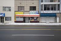 Detroit: paesaggio urbano d'inverno. Una strada deserta. Vecchi edifici. Un ristorante, una clinica, serrande abbassate e un cartello di affitto.
