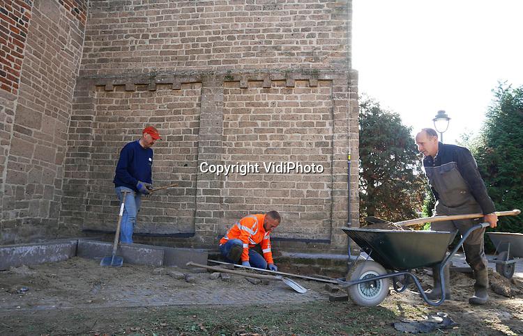 Foto: VidiPhoto<br /> <br /> VALBURG &ndash; De voltallige kerkenraad, predikant en een aantal vrijwilligers van de Hervormde gemeente Valburg-Homoet besparen de gemeenschap zaterdag duizenden euro&rsquo;s. Door jarenlange vochtophoping in de muren van de bijna 1000 jaar oude kerk, liet het stucwerk aan de binnenzijde los en raakten de middeleeuwse muurschilderingen aangetast. Door het pleisterwerk te verwijderen krijgen de muren nu ruim een jaar lang gelegenheid om het vocht kwijt te raken, waarna in 2019 of 2020 tijdens de tweede restauratiefase nieuw pleisterwerk en vloerverwarming wordt aangebracht. Om nieuwe vochtproblemen te voorkomen wordt nu rond de kerk drainage aangebracht door gemeenteleden zelf. Daarmee wordt zo&rsquo;n 20.000 euro bespaard, omdat ook veel straatwerk vernieuwd moet worden. Tijdens de graafwerkzaamheden zaterdag is een deel van een stenen kanonskogel gevonden. De Hervormde gemeente verwacht drie zaterdagen nodig te hebben om alles gereed te krijgen. Het historische godshuis wordt iedere zondag nog tweemaal gebruikt voor de eredienst. De restauratie wordt begeleid door ingenieursbureau Lakerveld uit Noordeloos.