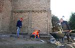 Foto: VidiPhoto<br /> <br /> VALBURG – De voltallige kerkenraad, predikant en een aantal vrijwilligers van de Hervormde gemeente Valburg-Homoet besparen de gemeenschap zaterdag duizenden euro's. Door jarenlange vochtophoping in de muren van de bijna 1000 jaar oude kerk, liet het stucwerk aan de binnenzijde los en raakten de middeleeuwse muurschilderingen aangetast. Door het pleisterwerk te verwijderen krijgen de muren nu ruim een jaar lang gelegenheid om het vocht kwijt te raken, waarna in 2019 of 2020 tijdens de tweede restauratiefase nieuw pleisterwerk en vloerverwarming wordt aangebracht. Om nieuwe vochtproblemen te voorkomen wordt nu rond de kerk drainage aangebracht door gemeenteleden zelf. Daarmee wordt zo'n 20.000 euro bespaard, omdat ook veel straatwerk vernieuwd moet worden. Tijdens de graafwerkzaamheden zaterdag is een deel van een stenen kanonskogel gevonden. De Hervormde gemeente verwacht drie zaterdagen nodig te hebben om alles gereed te krijgen. Het historische godshuis wordt iedere zondag nog tweemaal gebruikt voor de eredienst. De restauratie wordt begeleid door ingenieursbureau Lakerveld uit Noordeloos.