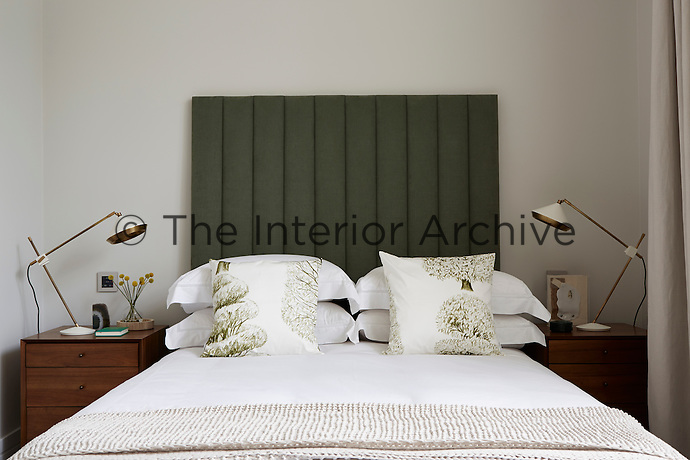 The guest bedroom is decorated in a white and green palette. The double bed has an upholstered headboard and a pair of angle-poise lamps on matching bedside chests stands on either side.