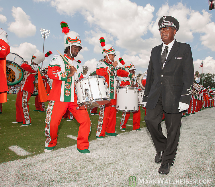 TALLAHASSEE, FL - SEPTEMBER 7, 2013:   <br /> Dr. Sylvester Young, director of marching and pep bands, walks along as the FAMU Marching 100 band performs on the field during the half time of the Florida A&amp;M Rattlers vs Tennessee State Tigers NCAA football game.   The temperature was 110 degrees on the filed.