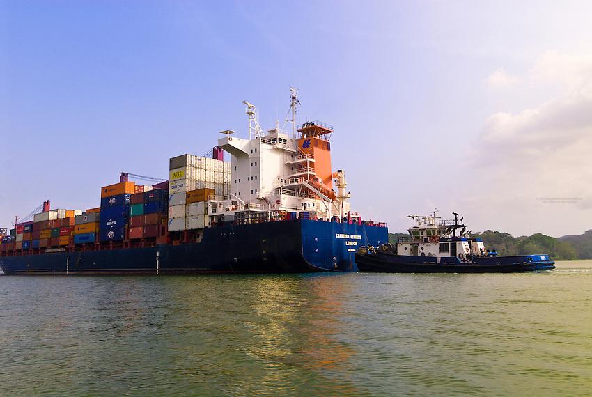 A container ship and a tugboat transit the Panama Canal (Gatun Lake), Panama