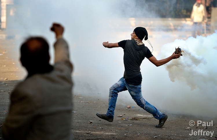A demonstrator prepares to hurtle a smoking tear gas canister back at police during November 27, 2012, protests in Cairo's Tahrir Square. The protestors were upset by Egyptian President Mohammed Mursi's November 22nd decision to assume sweeping new powers.