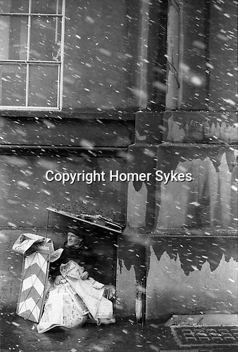 An Evening Standard newspaper street seller sheltering from the snow and covered up with the newspaper. Stamford Street London SE1  England 1975