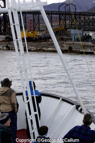 Ecotourists on ship bow approaching Pyramiden abandoned Russian mining town on Spitzbergen  Guide must carry a weapon as protection from Polar bears. Arctic Norway