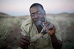 KUNENE, NAMIBIA - APRIL 24: Mannetje Ganaseb, age 42, a lead Rhino tracker for Save The Rhino trust, lights a cigarette in a resting camp on April 24, 2008 in Kunene, Namibia. He participated in a 2-week survey with a walking safari with camels and a crew through 155 miles of proposed parkland through the savanna at Etosha National park, through rocky badlands, across the world's oldest desert, the Namib and the blinding dunes and fogy cliffs at Skeleton Coast on the Atlantic Ocean. One of the missions was to track the black Rhinoceros who is now brought back from certain extinction, and more than one hundred fifty of them roam free in this remote area. (Photo by Per-Anders Pettersson).