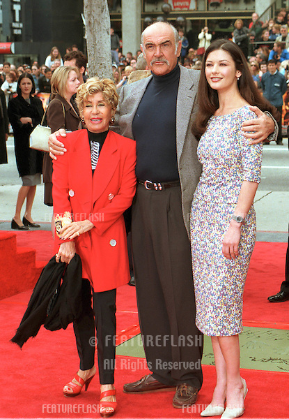 "13APR99:  Actor SEAN CONNERY, with wife Michelin (left) & actress CATHERINE ZETA JONES, at Hollywood's Manns Chinese Theatre where he had his hand & footprints set in cement. .His new movie, ""Entrapment,"" opens this week.    .© Paul Smith/Featureflash"
