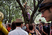 Spectators and bands gather in Davis Square for the start of the HONK! Festival in Somerville, Massachusetts, USA.  The HONK! Festival is an annual gathering of activist street marching bands that involves performances, a parade between Davis Square in Somerville and Harvard Square in Cambridge, and an academic symposium about street music.