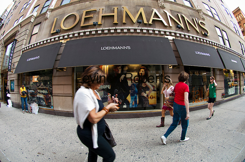 Shoppers enter and leave a Loehmann's department store in New York on Thursday, September 13, 2012.  (© Frances M. Roberts)