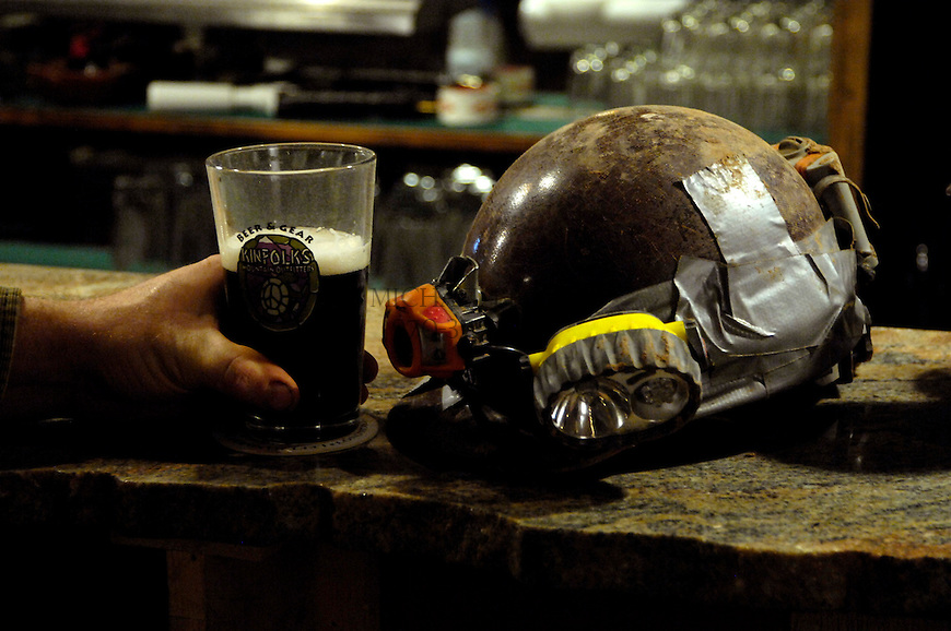 The ragged and work spelunkers helmet of Gordi Barker sits on the bartop of Kinfolks Mountain Shop. Barker is a hobbyist spelunker and decided to go out for a beer after an afternoon of caving. Kinfolks is a bar, music venue, and ourdoor gear shop. Michael Brands for The New York Times.