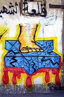 """A detail of a Hamas Mural in Gaza City shows a foot standing on a broken and bleeding David star. The detail is part of a graffiti remembering the Hamas martyr Amar Awad Al Yirjawi, a member of Hamas military wing  """"Asadin Al Qassam"""". ..""""The castle of the Qassamist Martyr Amar Awad Al Yirjawi"""" is written in the graffiti. Photo by Quique Kierszenbaum.."""