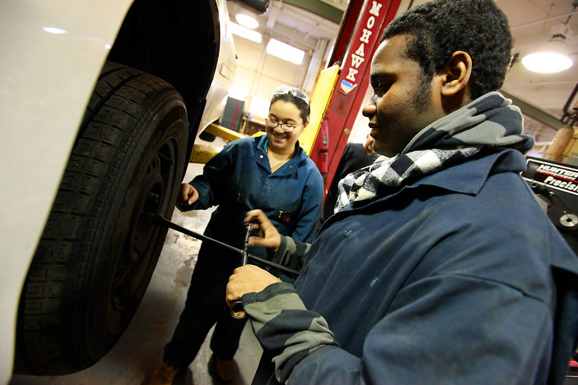 Automotive HS, Brooklyn, NY on Friday, January 22, 2010.  High school students have the opportunity to participate in a special program where they perform basic maintenance and repairs on privately owned cars at very competitive prices.  Students Naomi Saez, 17, left, and Kenny Ramdwar, 17, change the tire of a car..