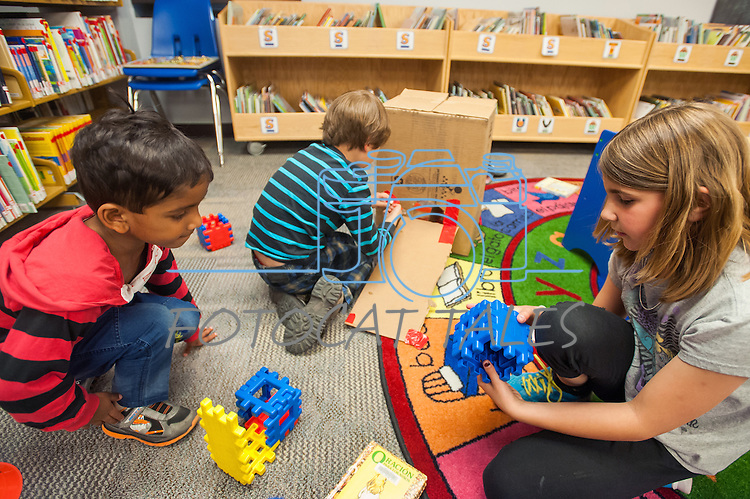 Alex Wells builds a obstacle with help from Sathvik Vadlakunta, left, and Sandra Tubiello during the Mini Golf Night at the Carson City Library on Friday, May 9, 2014. Kids and parents built a custom mini golf course throughout the library using anything at their disposal and engineering ideas to make a difficult course. Everything from tables to shelves were used to create creative courses.<br />