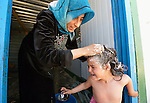 Jehan Hamza washes her 9-year old daughter Fareeza's hair in the Zaatari refugee camp near Mafraq, Jordan. The girl benefits from an anti-lice campaign sponsored by International Orthodox Christian Charities, a member of the ACT Alliance.<br /> <br /> Established in 2012 as Syrian refugees poured across the border, the Zaatari camp held more than 80,000 refugees by 2015, and was rapidly evolving into a permanent settlement. ACT Alliance member agencies provide a variety of services to refugees living in the camp.