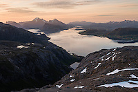Midnight sun light over Nappstraumen and distant mountains from summit of Hestræva, Flakstadøy, Lofotne Islands, Norway
