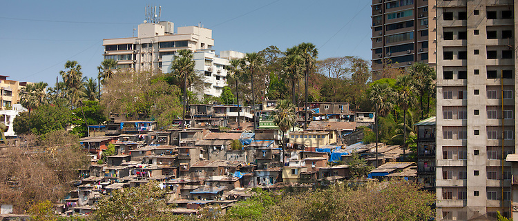 Slum housing and slum dwellers next to apartment blocks in Bandra area of Mumbai, India from Bandra Worli Sealink Road