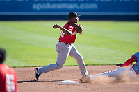 Vancouver Canadians shortstop Jesus Severino (10) throws to first base for a double play during a Northwest League game against the Spokane Indians at Avista Stadium on September 2, 2018 in Spokane, Washington. The Spokane Indians defeated the Vancouver Canadians by a score of 3-1. (Zachary Lucy/Four Seam Images)