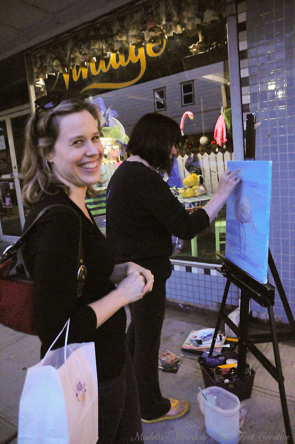 Nicole Notch encourages artist Sue Wachter as she participates in the dueling flamingos paint-off, organized by the Rectangle Gallery during Centralia, Washington's Third Thursday on September 15, 2016.