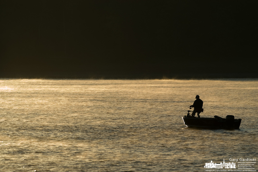 Lone fisherman on lake at sunrise in light fog
