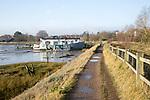 Houseboats moored by river wall River Deben, Melton, Suffolk, England, UK
