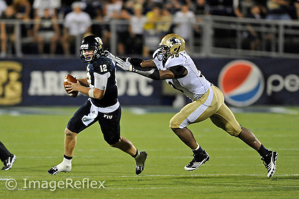 8 September 2012:  FIU quarterback Jake Medlock (12) attempts to evade Akron defensive lineman J.D. Griggs (90) in the fourth quarter as the FIU Golden Panthers defeated the Akron Zips, 41-38 (overtime), at FIU Stadium in Miami, Florida.