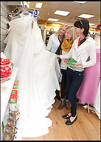 BNPS.co.uk (01202) 558833<br /> Picture: LauraJones/BNPS<br /> <br /> Eager customers Debbie Johnson, Stephanie Bossert and Denise Johnson looking through the wedding dresses.<br /> <br /> A charity shop is being besieged by bargain-hunting brides after a mystery donor gave them 100 new wedding dresses.<br /> <br /> Staff at the PDSA store in Boscombe, Bournemouth, Dorset, were shocked when they opened several cardboard boxes left for them to find the pristine wedding and bridesmaid gowns inside.<br /> <br /> The garments have a combined retail price of more than &pound;50,000 but the charity shop is selling them for huge discounted prices. One gown worth &pound;1,500 is for sale for &pound;250.