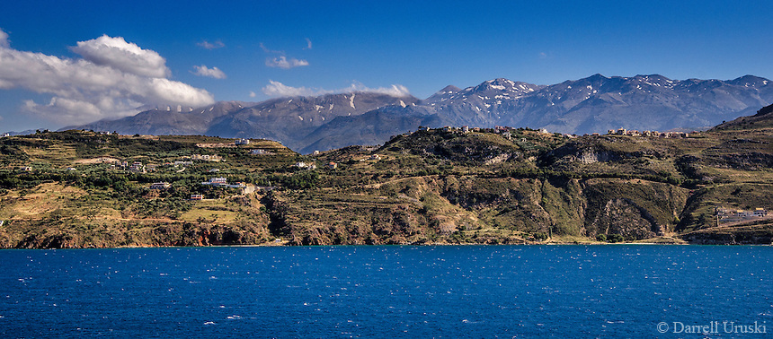 Landscape scenic of the beautiful Greek shoreline that is framed by the snow capped mountains and the green hillside dotted with homes overlooking the expansive ocean vista.