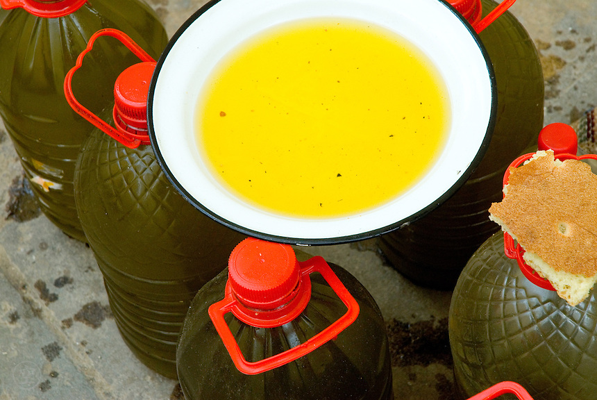 A sample bowl of yellow olive oil and bread to taste are placed on top of plastic bottles of oil in Fez, Morocco.