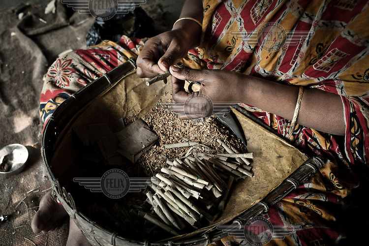 A woman, with the family name Chowduli, makes bidi cigarettes. Chowduli is a Muslim name and, although not part of the Hindu caste system, among Muslims they are stigmatised and the name is synonymous with low status. Consequently the West Bengal government has bestowed on them the status of 'backward'. This entitles them to positive discrimination when applying for government jobs and education.