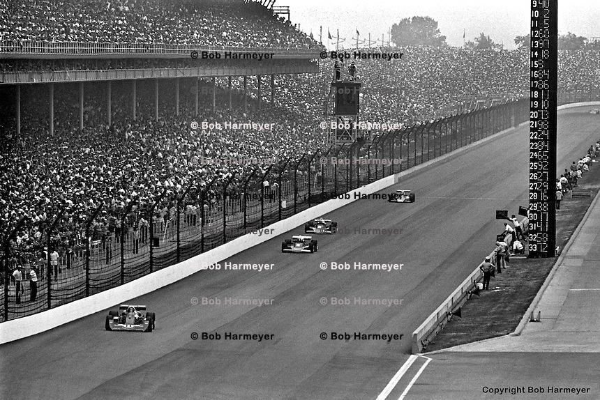 INDIANAPOLIS, IN: AJ Foyt leads a group of cars past the pit lane during the Indianapolis 500 on May 29, 1977, at the Indianapolis Motor Speedway.