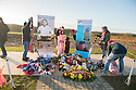 "25/12/14<br /> <br /> Football fans from around the world kick a football around and pay their respects by a makeshift shrine to the Christmas Day trucec football match in the field near Messine, Belgium, close to where the match was played in Flanders, Belgium.<br /> <br /> The sculpture, made in England, arrived in Flanders on Christmas Eve, and was first displayed in the town centre before being taken to the spot where the match was played. <br /> <br /> Sculpted by Andy Edwards the work is entitled 'All Together Now', recalling the song by the band The Farm - which was inspired by the truce. <br /> <br /> Chris Butler said: ""Castle Fine Arts are proud to have cast a number of war memorials over the years. We are honoured to support this sculpture for peace. I believe it will touch the hearts of millions.""<br /> <br /> <br /> ""It will be a symbol of peace and hope and a call for a renewed worldwide cessation of violence in honour of those brave boys who 'joined together and decided not to fight'"".<br /> <br /> <br /> The statue depicts the meeting of a British and a German soldier over a football, deep in the mud between the lines on that first Christmas of the war. The soldiers appear to be shaking hands but  are not not quite touching, forming a space in which a visitor can insert their own hand to complete the union.  A chance for a moments reflection on how far we are from true peace and brotherhood and the part each of us has to play in that dream. We want the work to stand as both a celebration of this inspirational and heroic event and as symbol of hope and peace. <br /> <br /> The project was instigated some years ago, with the support of the Football Asscociation (FA), as football's contribution to the First World War commemorations. <br /> <br /> All Rights Reserved - F Stop Press. www.fstoppress.com. Tel: +44 (0)1335 300098"