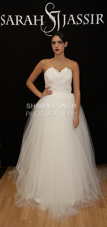 "Model poses in ""Iris"" - a tulle ball gown with organza ruched bodice and lace appliques, from the Sarah Jassir Fall 2013: From Concept To Creation collection, for her Angelique Bridal store opening at 6 East 45 Street, during New York Bridal Fashion Week, October 15, 2012"