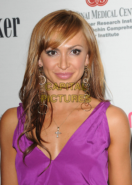 KARINA SMIRNOFF .at The 5th annual Pink Party celebration to Benefit Cedars-Sinai Women's Cancer Research Institute at the Samuel Oschin Comprehensive Cancer Institute, event held at La Cachette Bistro in Santa Monica, California, USA,.September 12th 2009.                                                                   .portrait headshot purple sleeveless v-neck cross necklace gold dangly earrings .CAP/DVS.©DVS/RockinExposuresCapital Pictures