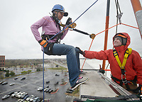NWA Democrat-Gazette/BEN GOFF @NWABENGOFF<br /> Rubianne Rubio of Bella Vista steps over the edge with guidance from volunteer Cambre Ricker of Fayetteville Saturday, March 11, 2017, during the Sunshine School &amp; Development Center's rappelling fundraiser with Over The Edge at the 8W Center in Bentonville. The school began a campaign in January, with participants who reached their fundraising goal able to participate in rappelling from the roof of the 6-story building. Over the Edge is a company which specializes in producing events for non profits using equipment and techniques used in commercial rope-access work such as sign installation and window washing. The event had raised more than $57,000 for the school, with more donations still coming in Saturday morning. Located in Rogers, the Sunshine School &amp; Development Center serves children and adults with developmental dissabilities, including a preschool.