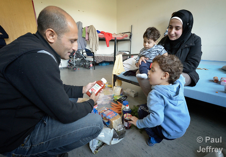 Farhan Othman (right) and her husband Ahmade Alkalil unpack their groceries from a shopping trip into nearby Messstetten, Germany, with help from their sons Suleiman, 3, and Mohammed, 1. Refugees from Syria, they have applied for asylum in Germany and are awaiting word on the government's decision. Meanwhile, they live in a room in a former army barracks in Messstetten.