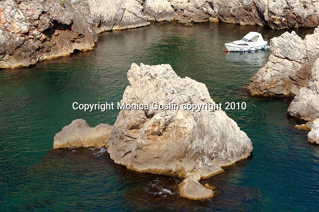A boat in the water, surrounded by jagged rocks, just outside the old city walls of Dubrovnik, Croatia.