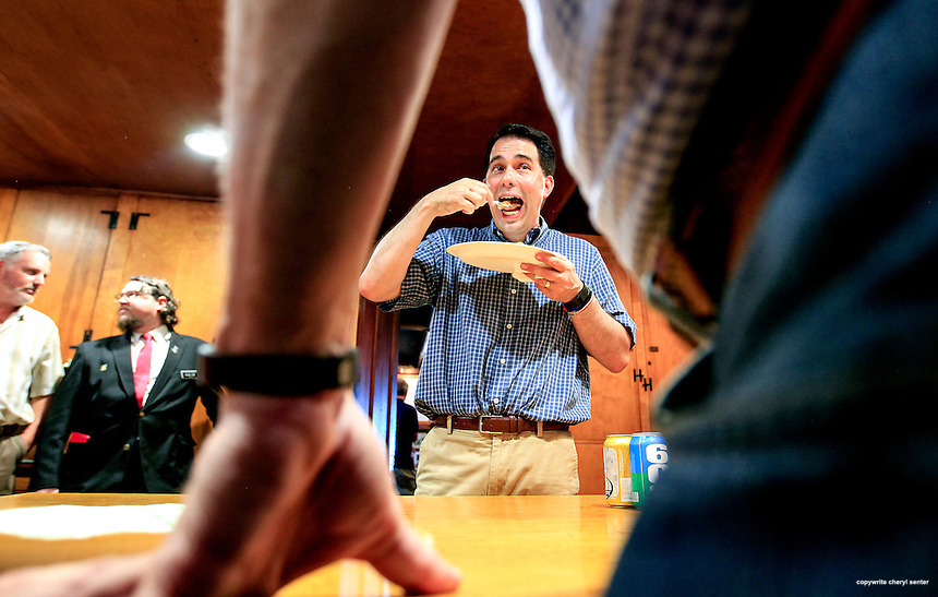 Concord, NH,  Saturday, May 30, 2015:  Wisconsin Gov. Scott Walker, center, spoons in a big mouthful of pie, part of the tradition of the event, after speaking at a Politics & Pies event held at the Snowshoe Club.  CREDIT: Cheryl Senter for The Boston Globe