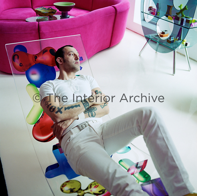 Portrait of interior designer Karim Rashid reclining on a perspex chair in his apartment