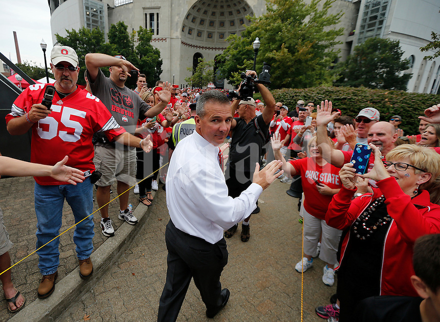 Ohio State Buckeyes head coach Urban Meyer looks back as he high fives fans while leading the team into Ohio Stadium before the college football game between the Ohio State Buckeyes and the Northern Illinois Huskies in Columbus, Saturday afternoon, September 19, 2015. (The Columbus Dispatch / Eamon Queeney)